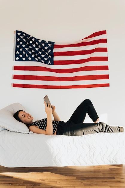 Улыбается женщина, лежа на кровати и с помощью планшета Бесплатные Фотографии