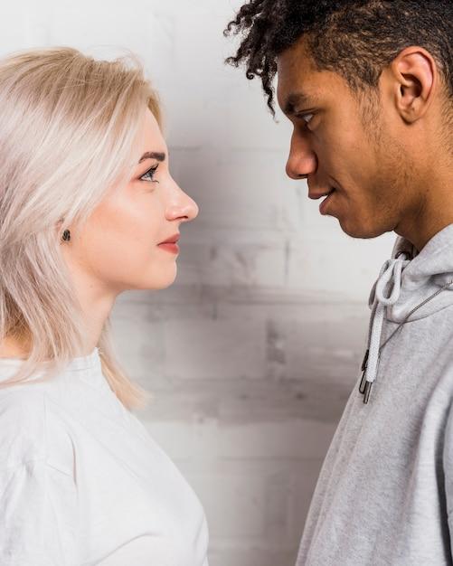 お互いを見て異人種間のカップルの友人の側面図 無料写真