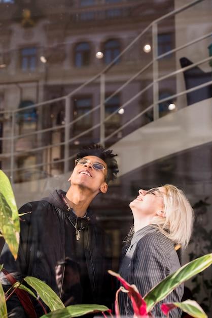 見上げるメガネをかけて魅力的な笑顔若いカップル 無料写真