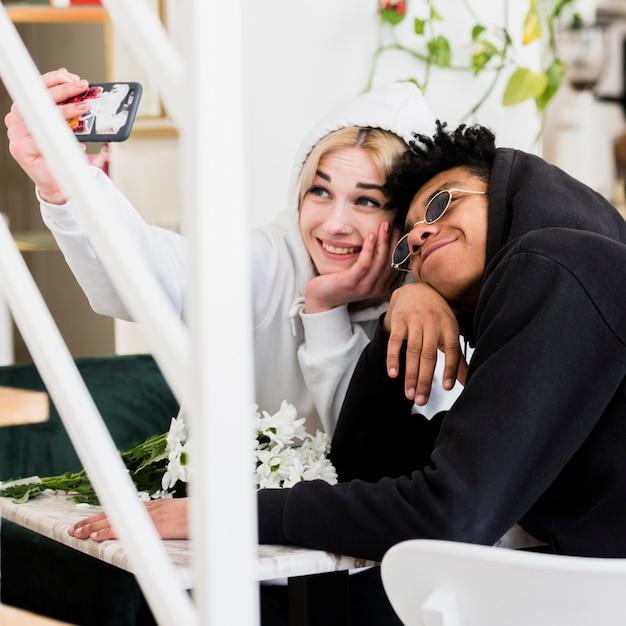 Милая счастливая межрасовая подростковая молодая пара, делающая селфи на мобильном телефоне Бесплатные Фотографии