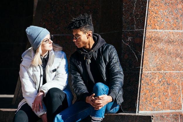 お互いを見て日光の下で座っている異人種間の若いカップル 無料写真