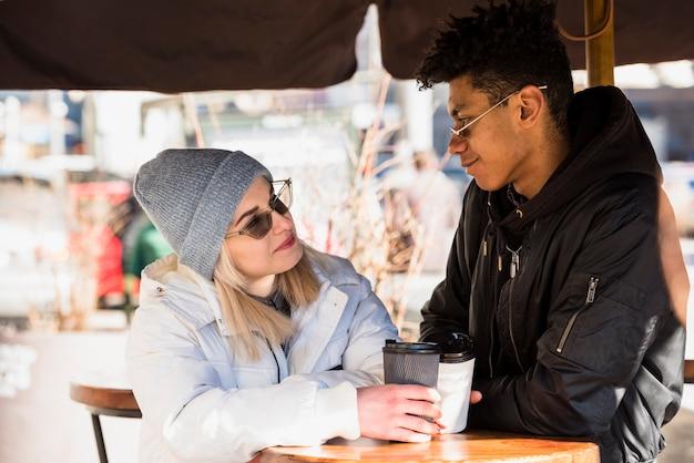 カフェに座っている使い捨てのコーヒーカップを保持している金髪の若い異人種間の若いカップル 無料写真