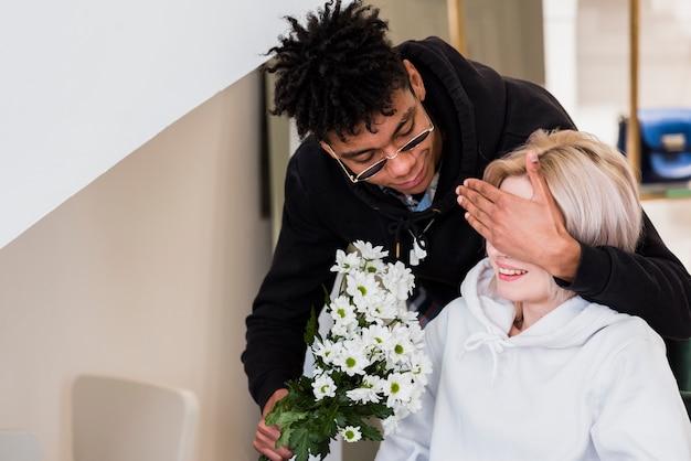 花の花束を手に保持している彼女のガールフレンドの目を閉じてアフリカの若い男 無料写真