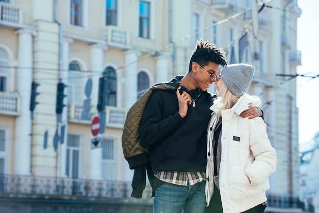 建物の前に愛する異人種間の若いカップルの立っています。 無料写真
