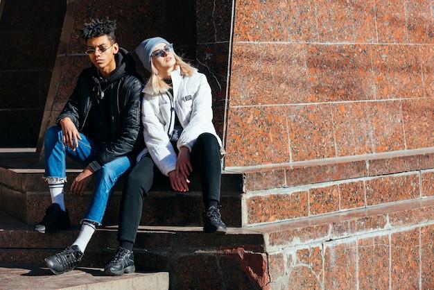 屋外に座っているファッショナブルな異人種間の若いカップルの肖像画 無料写真
