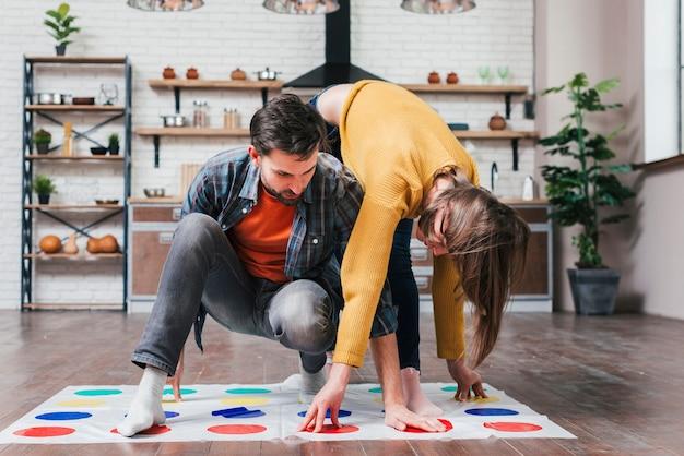 Молодой человек играет в твистер с женой дома Бесплатные Фотографии