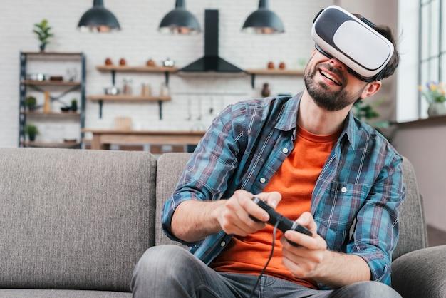ビデオゲームをプレイソファーに座っていたバーチャルリアリティ眼鏡をかけている若い男の笑みを浮かべてください。 無料写真