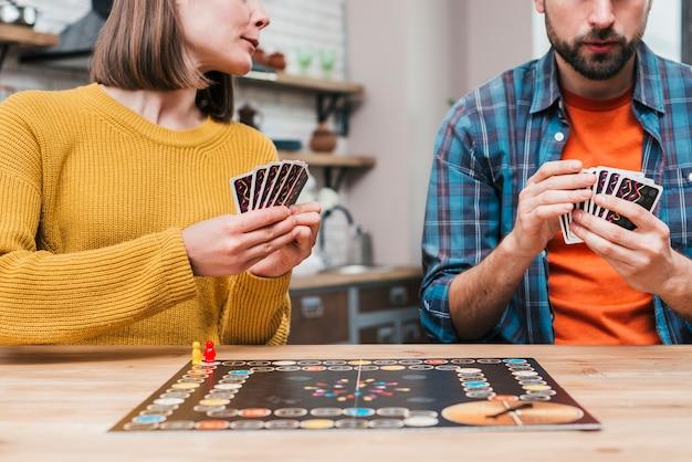 若いカップルが木製の机の上のボードゲームをプレイ 無料写真