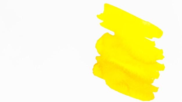白い背景に分離された黄色のブラシストローク 無料写真