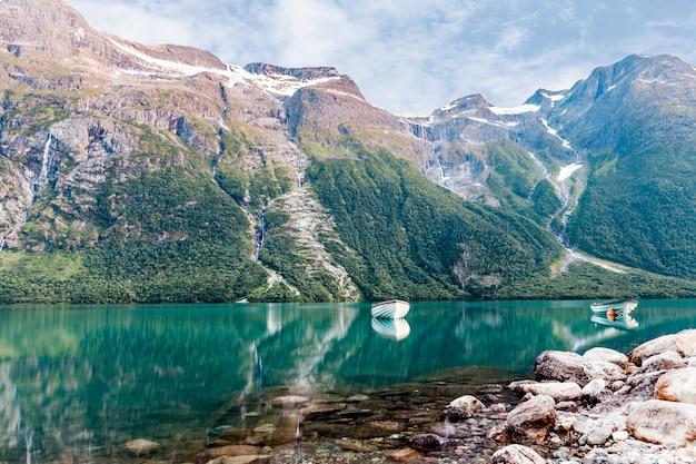 岩の山の近くののどかな湖の空の航海船 無料写真