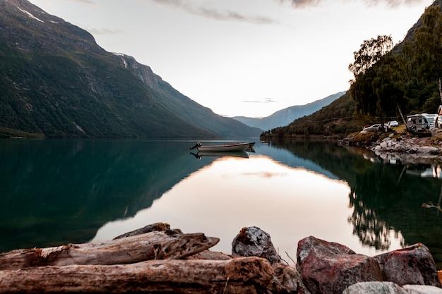 山と穏やかな湖のボートの反射 無料写真