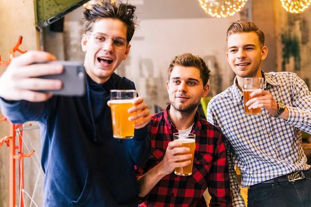 Улыбающиеся молодые друзья-мужчины, держа бокалы пива, принимая селфи на мобильный телефон Бесплатные Фотографии