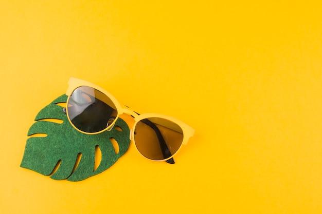 黄色の背景にサングラスをかけたグリーンモンステラの葉 無料写真