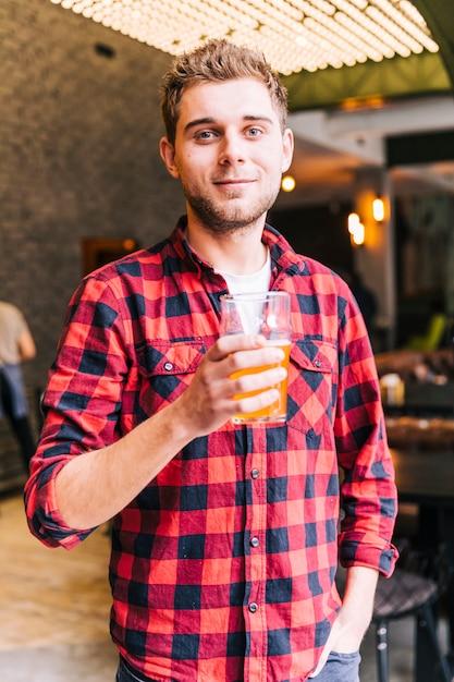 Портрет счастливого молодого человека держа бокал пива смотря камеру Бесплатные Фотографии