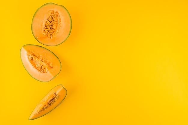 Ломтики плодов дыни на желтом фоне Бесплатные Фотографии