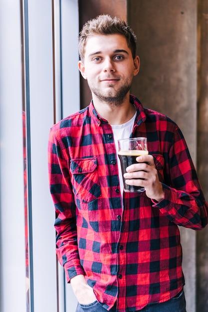 カメラを見てビールのグラスを保持している若い男の肖像 無料写真