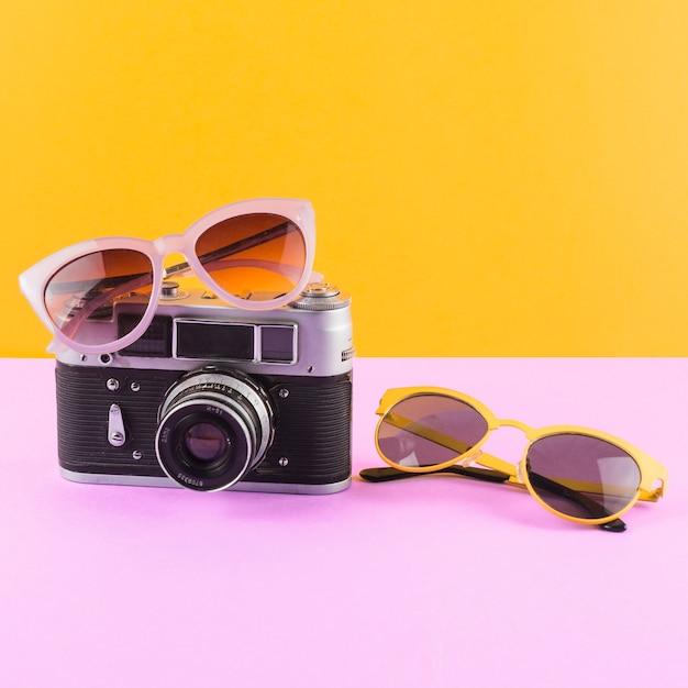 黄色の背景にピンクの机の上のカメラとサングラス 無料写真