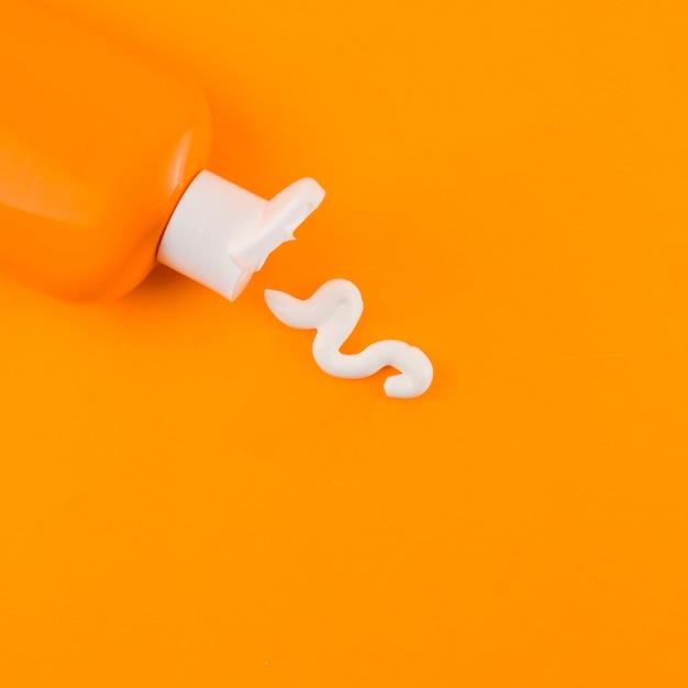 オレンジ色の背景に対してオレンジ色の瓶から出てくる白い日焼け止めクリーム 無料写真