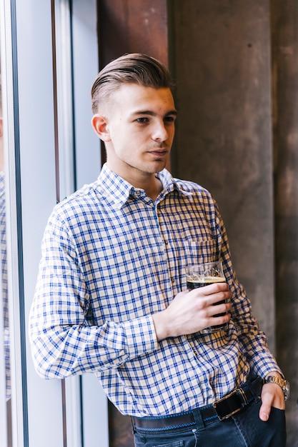 ビールのグラスを手に持ってウィンドウで傾いている思いやりのある若い男の肖像 無料写真