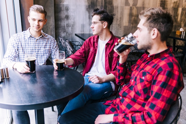Молодые люди сидят вместе пьют пиво со своим другом Бесплатные Фотографии