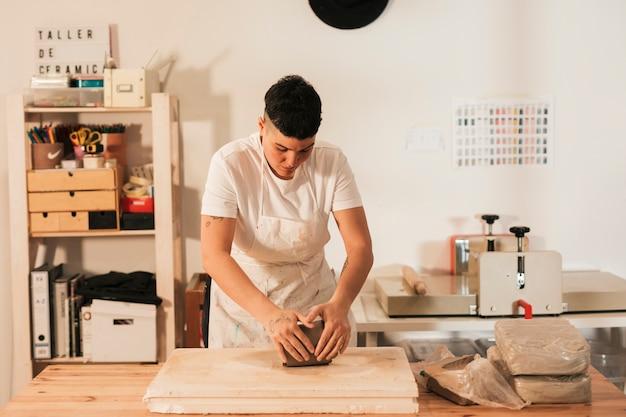 ワークショップで木の板に粘土を混練職人の手のクローズアップ 無料写真