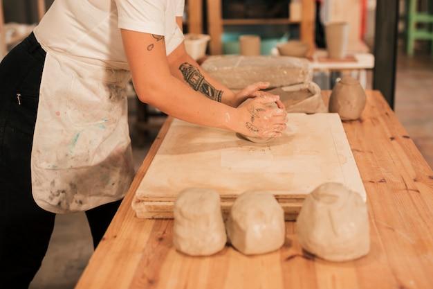 テーブルの上の木の板に粘土を混練の職人 無料写真