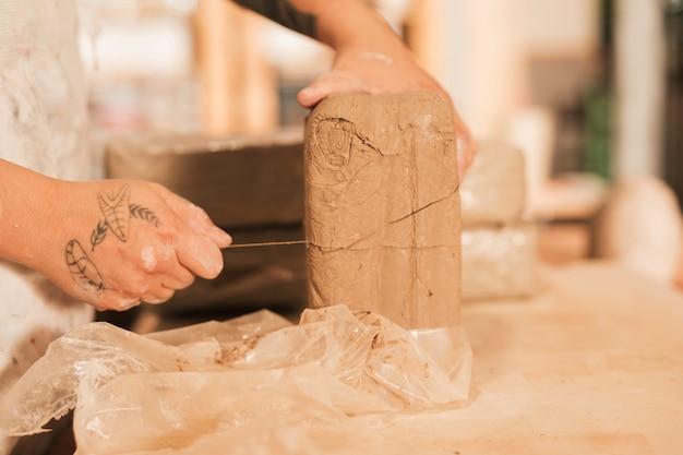 木のテーブルにスレッドで粘土を切る女性の手のクローズアップ 無料写真