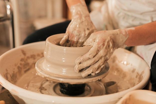 陶器のホイールに粘土で女性の陶工の手の成形のクローズアップ 無料写真