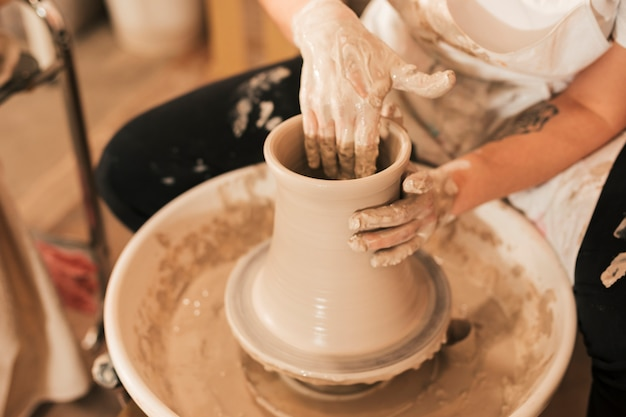 Рука женского гончара делает керамический горшок с глиной на гончарном круге Бесплатные Фотографии