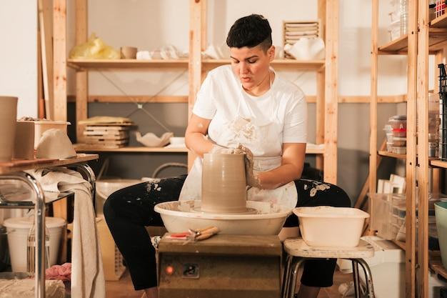 陶器のホイールに取り組んでいる女性の陶工 無料写真