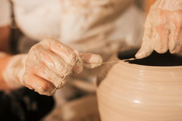 陶芸家は回転する輪に糸で陶器の縁を切ります 無料写真