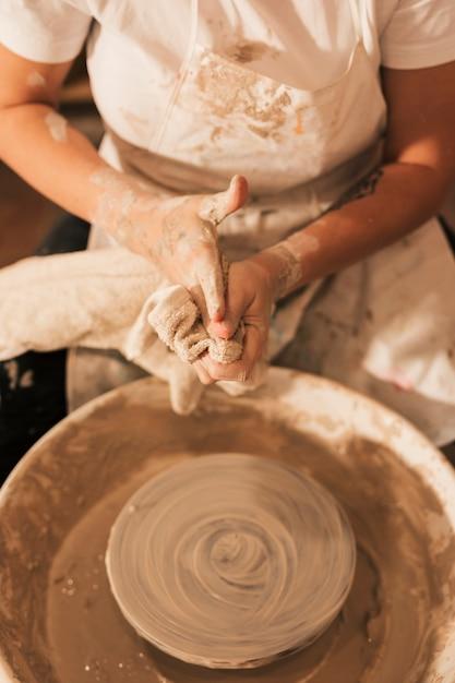 ナプキンで彼女の手を掃除する陶器のホイールの近くに座っている女性の陶工 無料写真