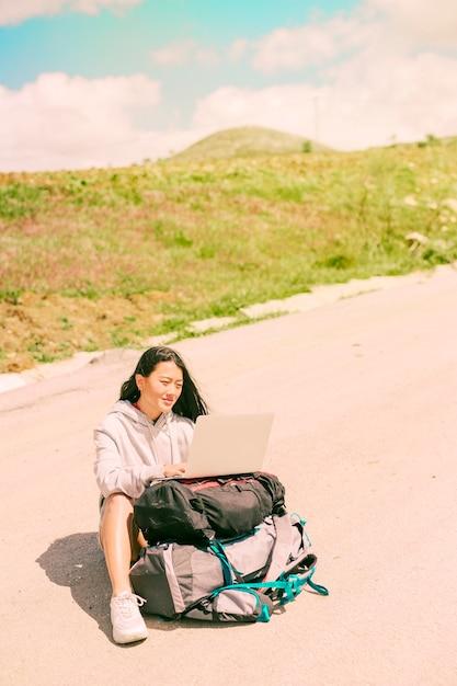 道路上に位置し、バックパックに置かれたラップトップに取り組んでいる女性 無料写真