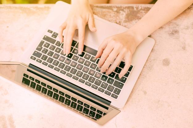 認識できない女性の屋外のノートパソコンのキーボードで入力します。 無料写真