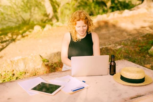若い女性の自然の机でラップトップ上でフリーランス 無料写真