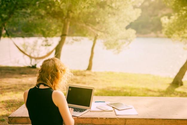 認識できない女性の机に座っていると自然の中でラップトップに取り組んで 無料写真