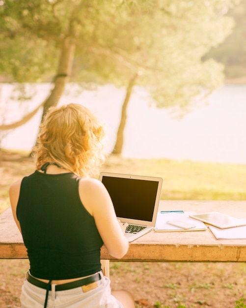 顔の見えない女性に座っていると絵のような場所でラップトップに取り組んで 無料写真