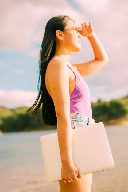 アジアの女性のラップトップを押しながら太陽を見て 無料写真