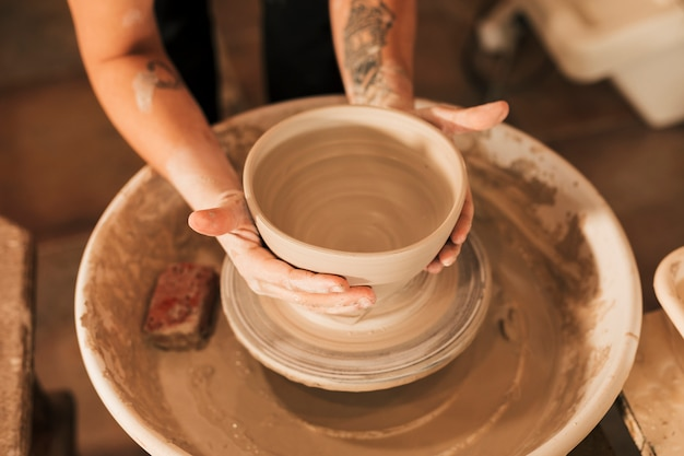 陶器のホイール上の粘土のボウルに形を与える女性の陶工の手のクローズアップ 無料写真