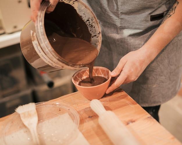 木製のテーブルの上にボウルに茶色の塗料を注ぐ女性の陶工の手のクローズアップ 無料写真