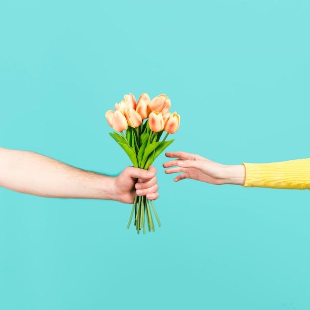 花のブーケを提供する手 無料写真
