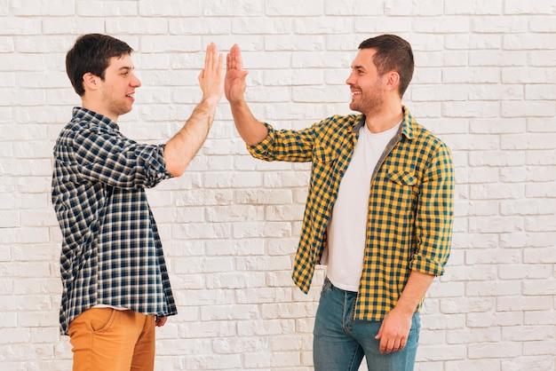 お互いにハイタッチを与える笑顔の若い男性の友人の側面図 無料写真