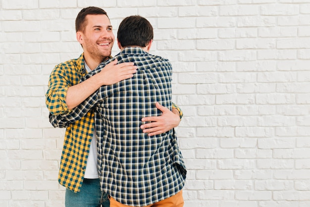 白いレンガの壁に彼の友人に抱擁を与える男の笑みを浮かべて肖像画 無料写真