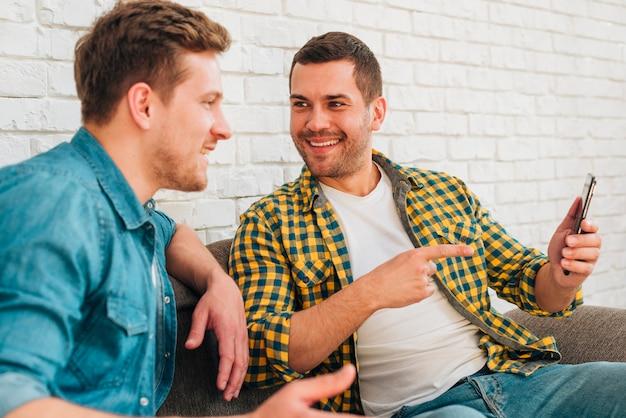 携帯電話で彼の指を指している彼の笑顔の友人を見ている男 無料写真