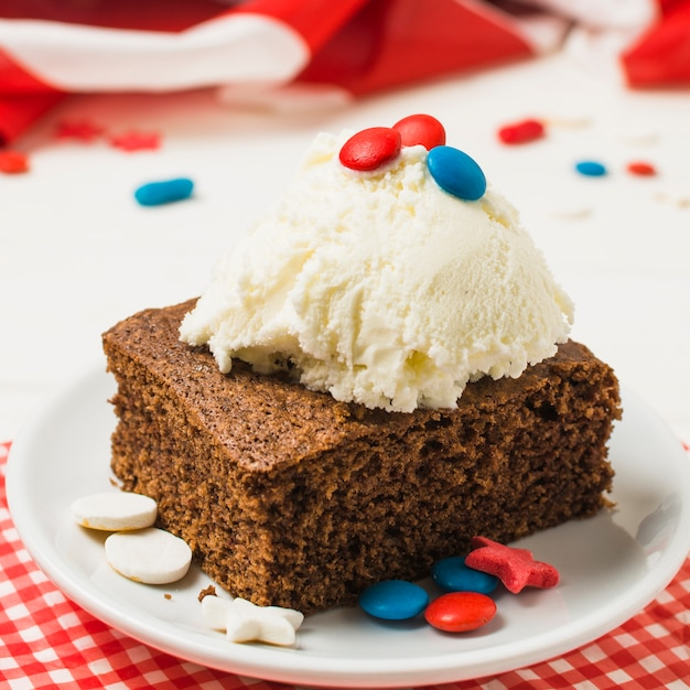 Вкусный торт с шариком мороженого и конфетами на белой тарелке на день независимости Бесплатные Фотографии