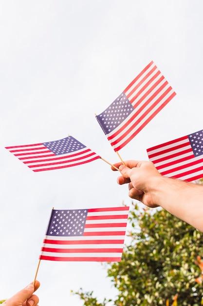 Низкий угол зрения мужской руки, держащей флаги сша Бесплатные Фотографии