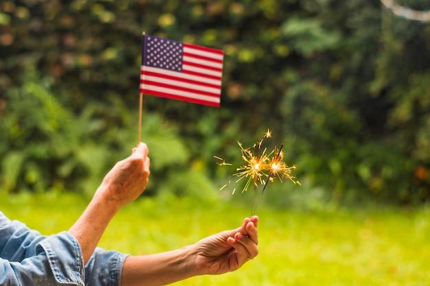 Конец-вверх женщины празднуя день независимости держа флаг сша и искры огня Бесплатные Фотографии