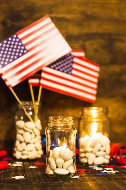 Заполненная баночка конфет с зажженными свечами и флагами сша на деревянном столе Бесплатные Фотографии