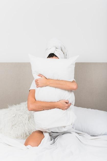 彼女の顔の前に白い枕を持ってベッドに座っている女性 無料写真