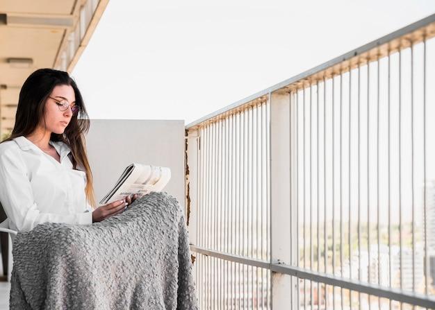 新聞を読んでバルコニーに座っている美しい若い女性 無料写真